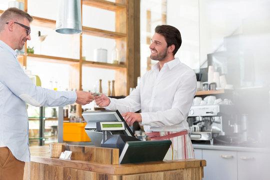 Customer paying worker at cafe cash register