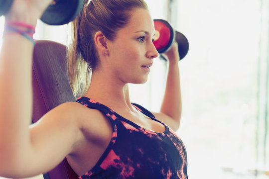 Focused woman doing dumbbell shoulder presses