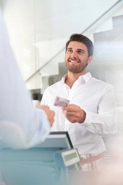 Worker giving customer change at cafe cash register
