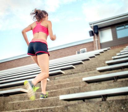 Young woman running stadium stairs