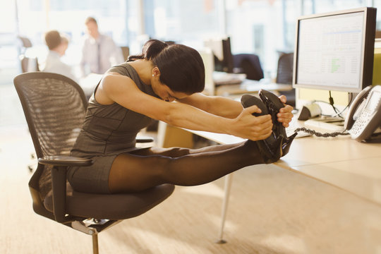 Businesswoman stretching legs with feet up on desk in office