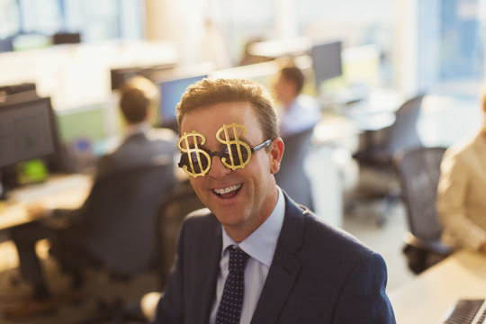 Portrait smiling businessman wearing dollar sign sunglasses in office