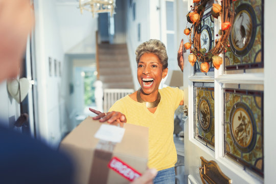 Enthusiastic woman receiving package delivery at front door
