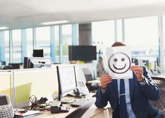 Portrait businessman holding smiley face printout over his face in office