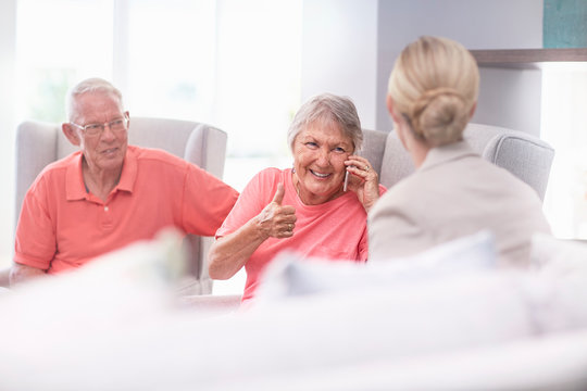 Senior woman talking on cell phone gesturing thumbs up