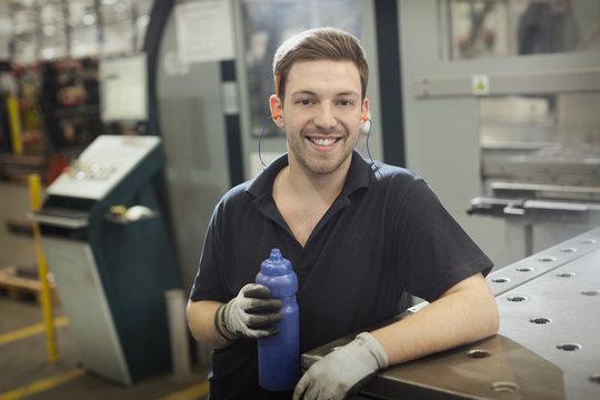 Portrait smiling worker with water bottle in steel factory