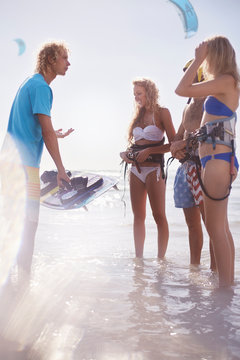 Man teaching friends kiteboarding in ocean surf