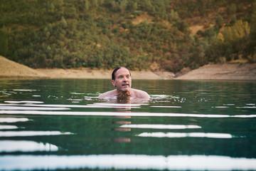Mature man swimming in lake