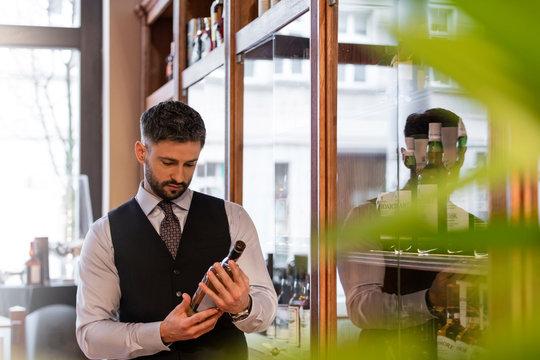 Well-dressed bartender examining whiskey bottle