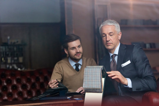 Tailor and businessman browsing fabric in menswear shop