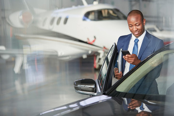 Businessman cell phone getting into car near corporate jet in hangar