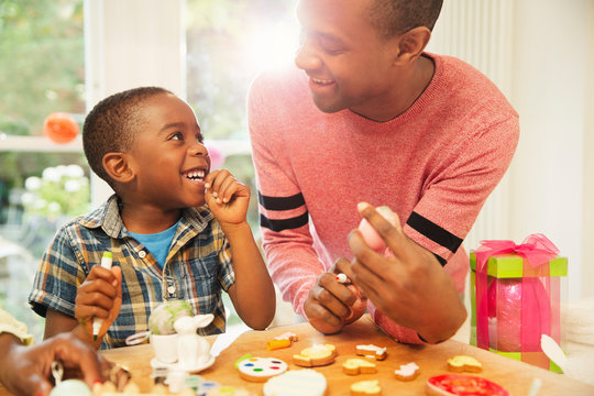 Smiling father and son decorating Easter eggs and cookies