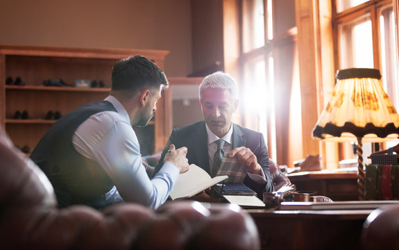 Tailor and businessman viewing fabric in menswear shop