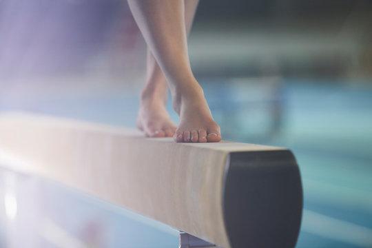 Bare feet of female gymnast performing on balance beam