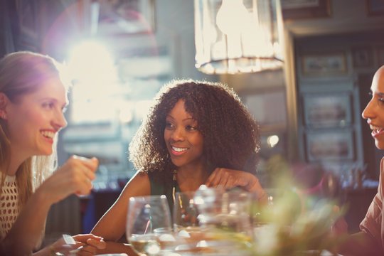 Smiling women friends dining and talking at restaurant table