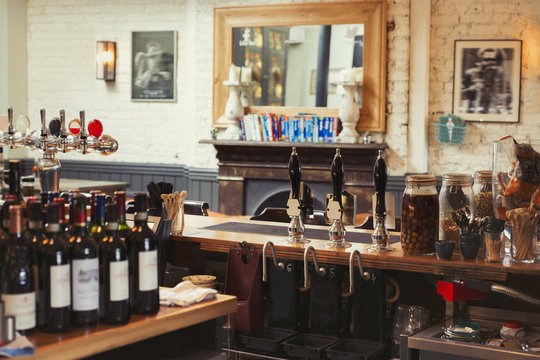 Wine bottles and tap handles behind bar in empty pub