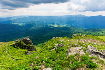 mountain landscape in summer. view from the top of carpathian watershed ridge in to the distance. boulders on the green grassy slopes. sunny weather with clouds on the blue sky