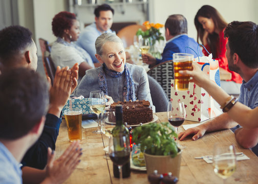 Woman enjoying birthday with friends at restaurant table