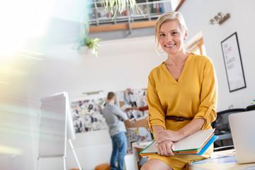 Portrait smiling female design professional leaning on office desk