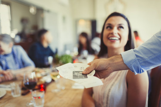 Waiter returning bill credit card to woman dining at restaurant table