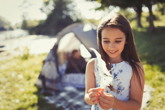 Smiling girl holding white feather outside sunny campsite tent