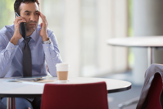 Stressed businessman talking on cell phone at table