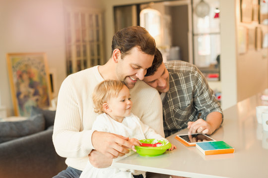 Male gay parents feeding baby son and using digital tablet