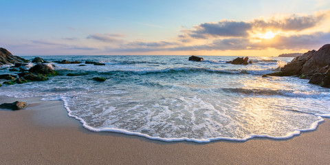 Spoed Fotobehang Strand sunrise on the beach. beautiful summer scenery. rocks on the sand. calm waves on the water. clouds on the sky. wide panoramic view