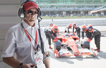 Portrait serious manager with formula one race car pit crew