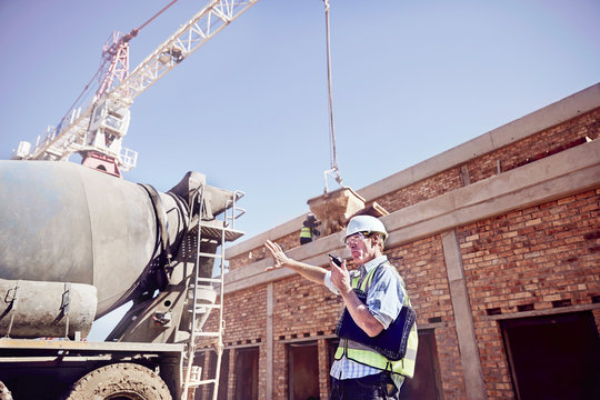 Construction worker foreman using walkie-talkie at sunny construction site