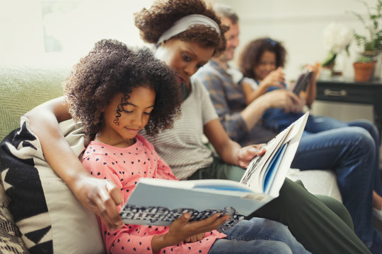 Parents reading books with daughters on living room sofa