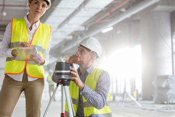 Engineers with digital tablet theodolite surveying construction site