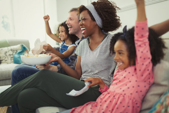 Enthusiastic multi-ethnic young family cheering, watching sports on sofa