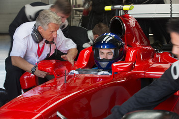 Manager talking to formula one race car driver in repair garage