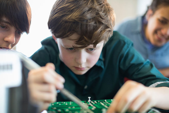 Focused boy student assembling electronics in classroom