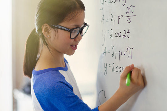 Portrait smiling, confident girl student solving physics equations at whiteboard in classroom