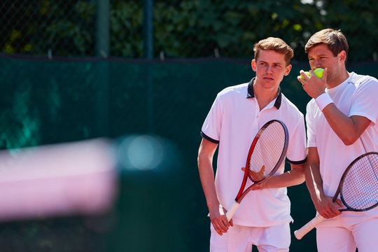 Young male tennis doubles players talking, strategizing
