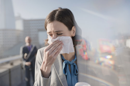 Businesswoman allergies blowing nose into tissue on sunny urban sidewalk