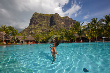 Woman in the swimming pool of Dinarobin Beachcomber at Le Morne Brabant, Mauritius
