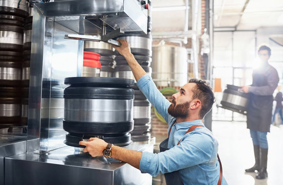 Male brewer filling kegs in brewery