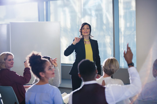 Businesswoman leading meeting, answering audience questions