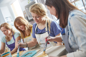 Female artists painting picture frames in art class workshop