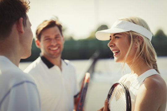 Male and female tennis players talking on tennis court