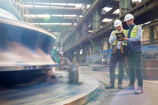 Male foreman and engineer with digital tablet talking in factory