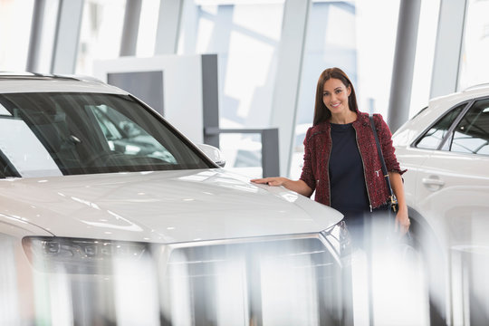 Portrait smiling female customer browsing new cars in car dealership showroom