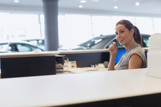 Smiling female receptionist talking on hands-free device telephone in car dealership showroom