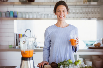 Portrait confident, smiling woman drinking healthy carrot juice in kitchen