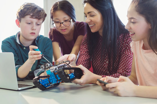 Female teacher students programming assembling robotics in classroom
