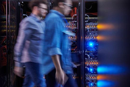 Male IT technicians walking in dark server room