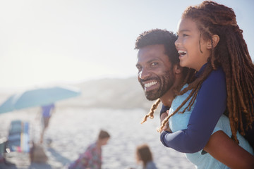 Portrait happy father piggybacking daughter on sunny summer beach